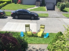 Lounge chairs set up on grass between sidewalk and street