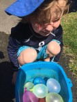 Four year old crouching next to container filled with water balloons