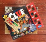 Run Yourself Ragged game in box, Clue Junior game in box, football peg game, and Driven tiny trucks in stack