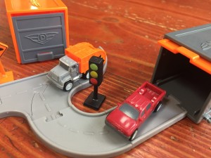 Driven Pocket series tiny trucks red pickup and orange garbage truck with small garage doors on connecting gray road pieces