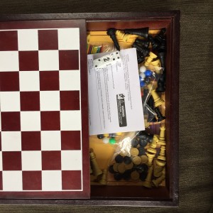 Five game in one box checkerboard lid slid open to reveal instructions and pieces for backgammon, chess, checkers, Chinese checkers, and pickup sticks