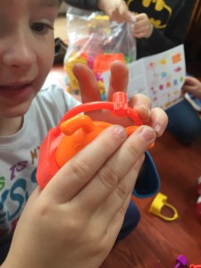 Child holding up orange dog in ferris wheel seat Gears! Gears! Gears! pet play land building set from Learning Resources