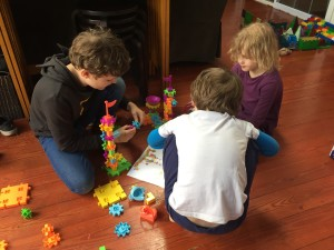 Nine year old, seven year old, and five year old kid assembling gears pet playland building set
