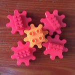 Toy gears in red and orange with Lego and Duplo bricks built in attached
