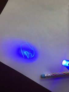 Invisible ink pen writing shown by blacklight on cap of pen