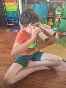 Child looking through toilet paper tubes as binoculars