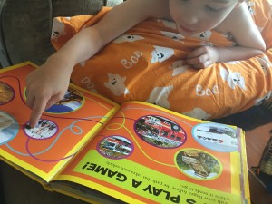 Child interacting with National Geographic Little Kids First Big Book of Things That Go