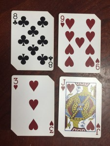 Playing cards laid out in two rows of two to make math problems