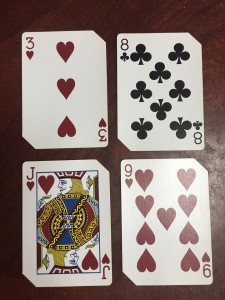 Playing cards laid out in two rows of two to make two digit numbers for Nifty 50 card game