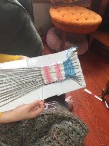 Child weaving project on homemade loom