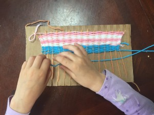 Child weaving pink white and blue project on homemade cardboard loom