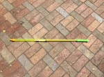 Super water saber gun blaster tube yellow with green handle on brick patio background