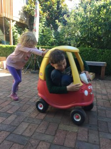 Big kids playing pushing Little Tikes Cozy Coupe red car on patio