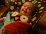 Hug and Hide Owl toy by Skip Hop with smiling baby in Fisher Price Woodland Friends bouncy seat