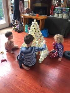 Kids using empty yogurt cups as building blocks toys