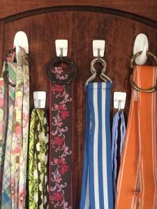 Belts hanging on command hooks inside closet door