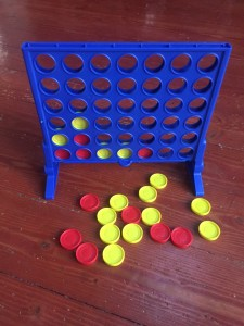 Connect 4 game in progress with red and yellow pieces dropped into blue board with holes