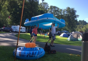 Adults carrying H20Go Bahama Wave Island Float at campsite