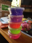 DIY Slime Kit six small brightly colored containers of slime stacked vertically on table