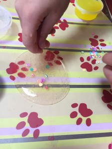 DIY Slime Kit from Zen Laboratories child adding tiny plastic food pieces to clear slime on plastic placemat
