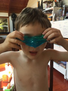 Child holding blue slime in front of eyes
