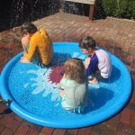 Jasonwell sprinkler play mat light blue with shark in middle and three kids sitting in it