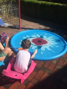 Kids lounging in chairs around Jasonwell Splash pad sprinkler play mat