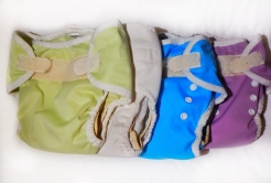 Cloth diapers Thirsties diaper covers folder and lined up on changing table