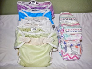 Thirsties cloth diaper covers stuffed with inserts next to stack of Honest disposable diapers