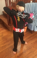 Eight year old girl dressed up in ninja costume with black face mask