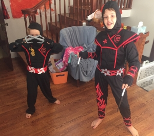 Two kids dressed up in black ninja costumes with red accents