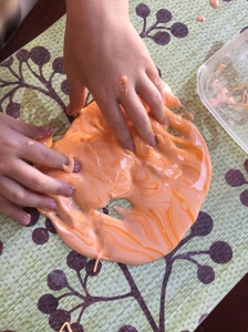 Orange gloop from Usborne 50 Science Projects for Kids book child playing in sensory material on mat