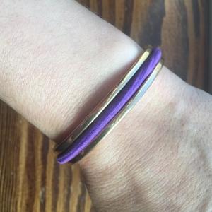 Purple hair elastic in hair tie bracelet worn on wrist