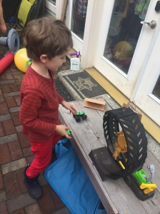 Child playing with Hot Wheels Monster Truck Epic Loop Challenge Set outside on bench