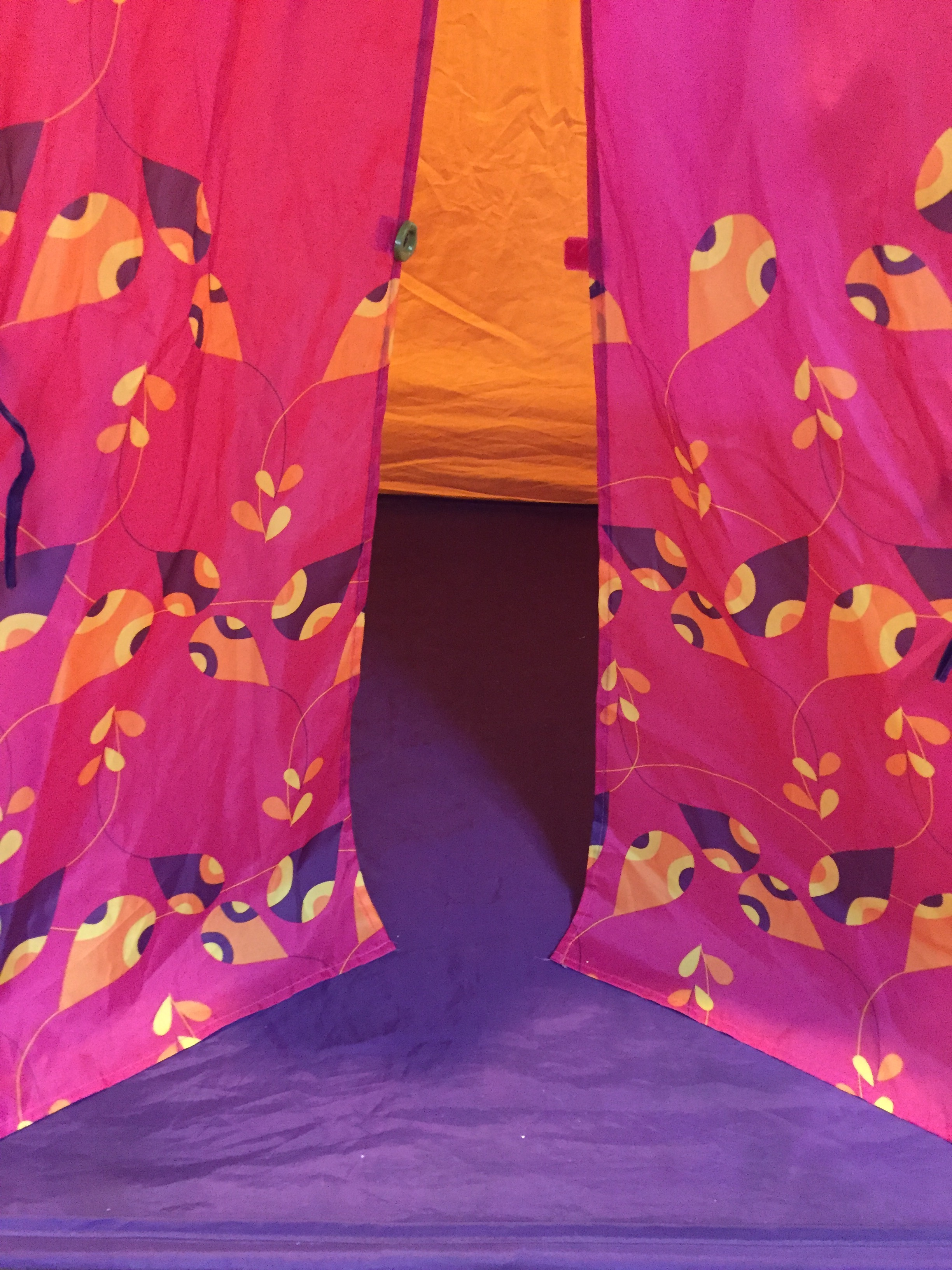 Kid's play tent with purple floor and orange walls with pink