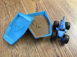 Monster Jam Kinetic Sand Starter Set with container mold, dirt sand, and blue shark monster truck