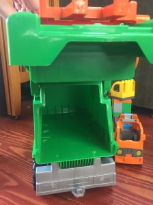 Open back end of Androni Giacattoli ecological recycling truck lifted by child's hand next to Duplo blocks