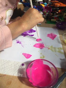 Child painting on paper by using straw to blow air to move paint