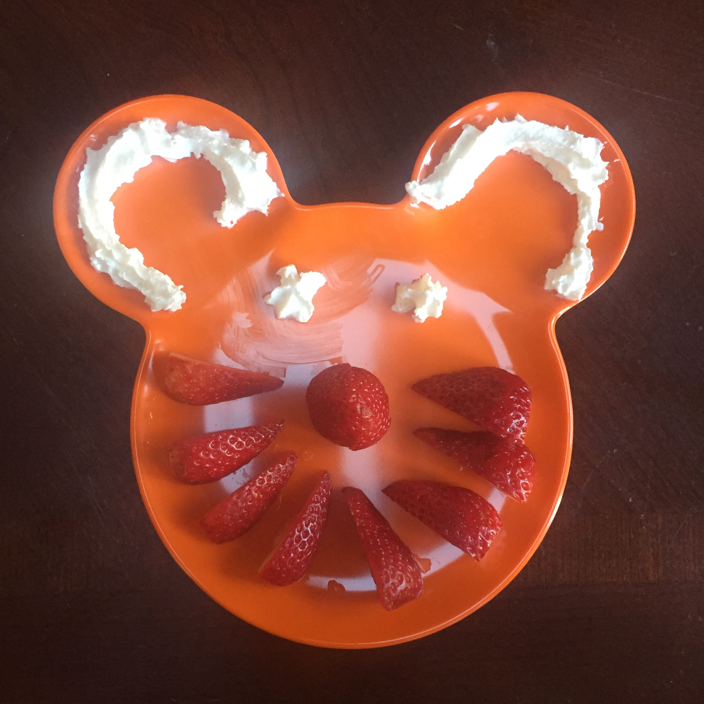Cut up strawberries sliced and arranged on orange Mickey Mouse head shaped plastic kids' plate with whipped cream for eyes and ears