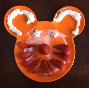 orange plastic kids Mickey Mouse shaped plate with sliced strawberries and whipped cream to make face for snack