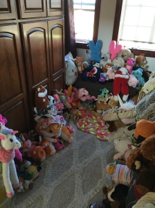 Kids stuffed animal museum display with critters sitting on floor, chaise lounge sofa, bed, rug and more covered with toys