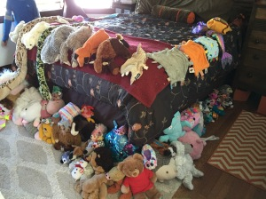 Stuffed animals set up on display on bed sorted by type size and color