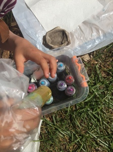 Child reaching into plastic container for colored dye in bottle from Tulip Tie-Dye Kit Party Box