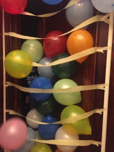 Ten year old kid opening door to cascade of birthday balloons falling