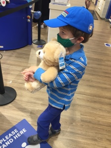 Child hugging stuffed birthday bear at Build-A-Bear store