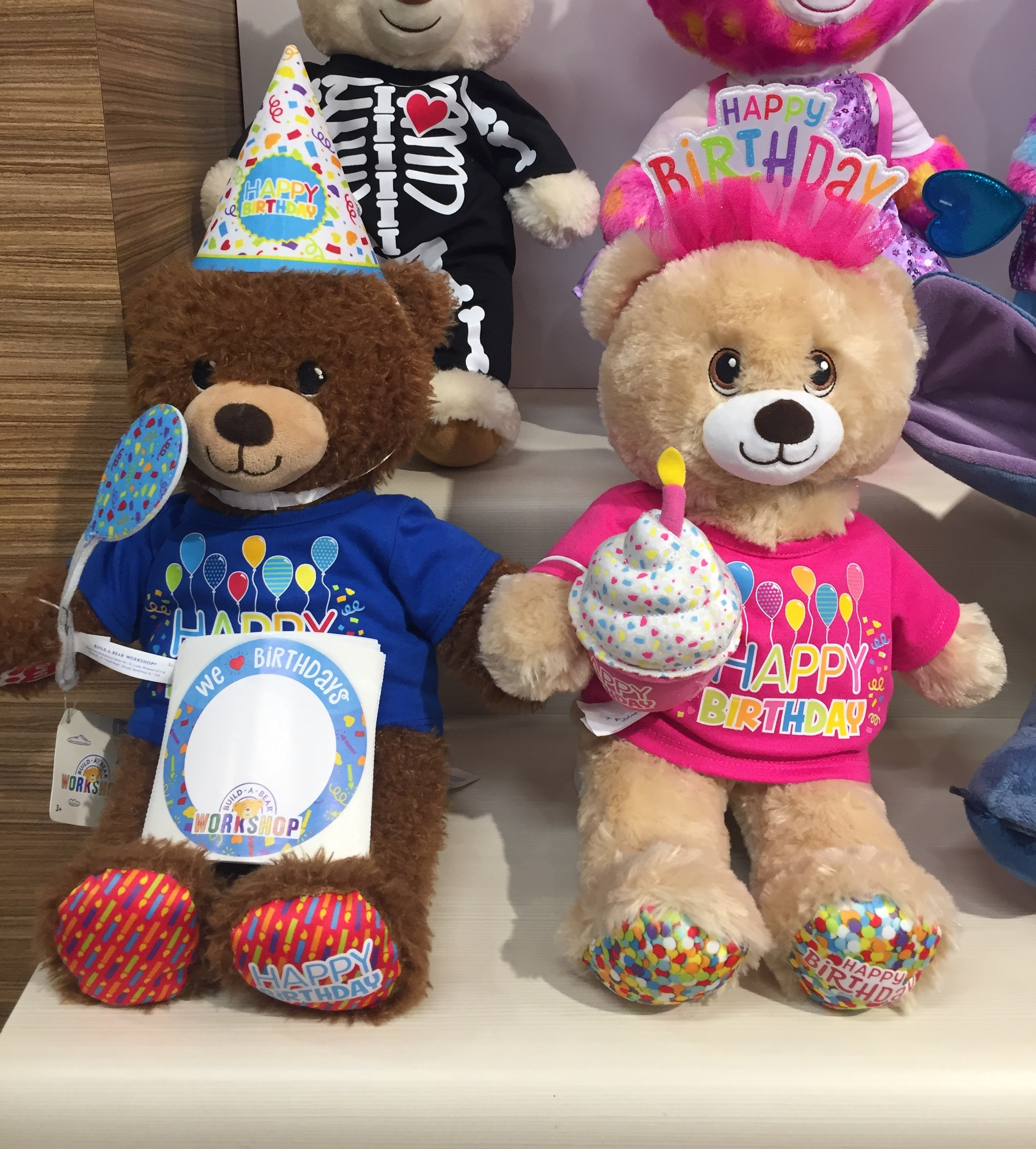 Build-A-Bear Birthday bears dressed in t-shirts and hats at store