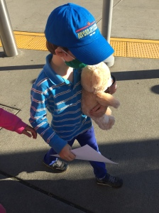 Six year old boy walking with Build-A-Bear birthday bear and certi