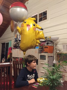 Pikachu and Poke ball balloons tied to chair with child sitting underneath
