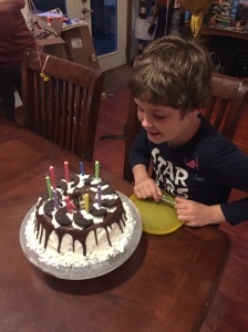 Ten year old boy blowing out birthday candles on mint chocolate chip homemade ice cream cake
