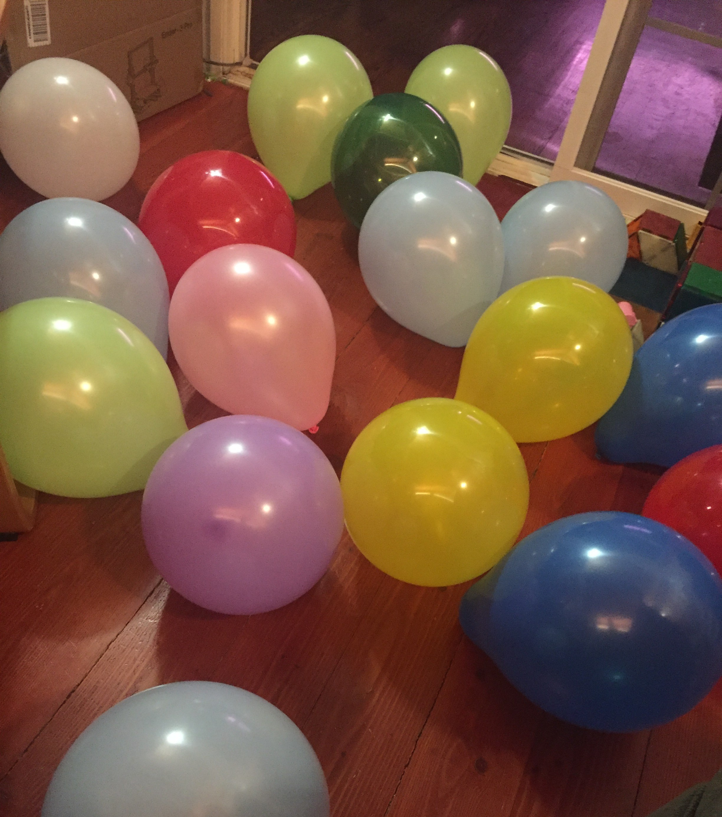 Birthday balloons inflated and scattered over hardwood floor